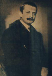 Porträt von Fürst Kinsky. Mann mit Schnauzbart und Kurzhaarschnitt trägt ein weißes Hemd, Krawatte und Mantel.